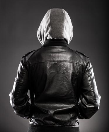 chaqueta de cuero: Hombre joven en la chaqueta de cuero y trasera capucha en la espalda