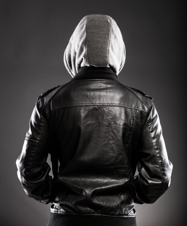 man rear view: Young man in leather jacket and hood rear view on back Stock Photo