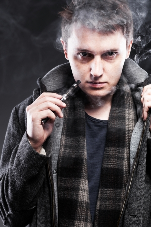 Young man smoking electronic cigarette photo