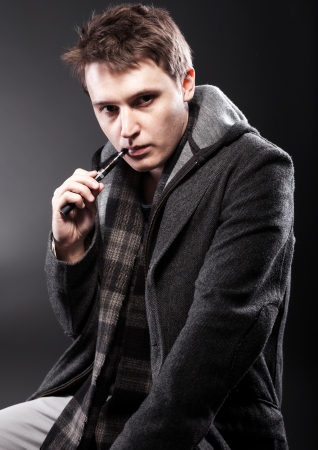 puffing: Young man smoking electronic cigarette