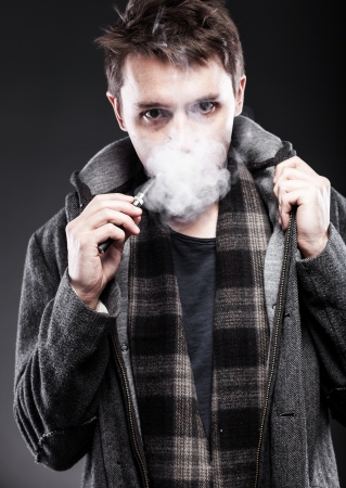 glycol: Young man smoking electronic cigarette