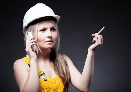Young architect woman construction worker smoking cigarette and talking on phone photo