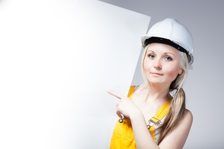 Young builder woman construction worker and empty banner
