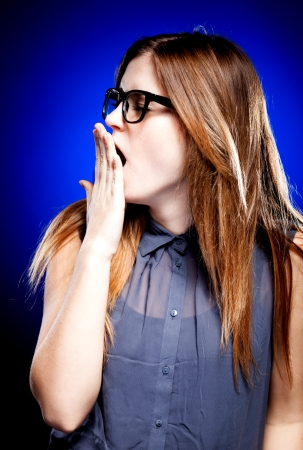 nerd glasses: Bored young woman with large nerd glasses yawning