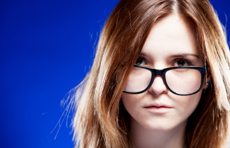 Closeup strict young woman with large nerd glasses photo