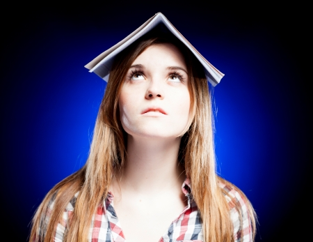 Confused and upset young girl holding exercise book on her head, symbol of school problems photo