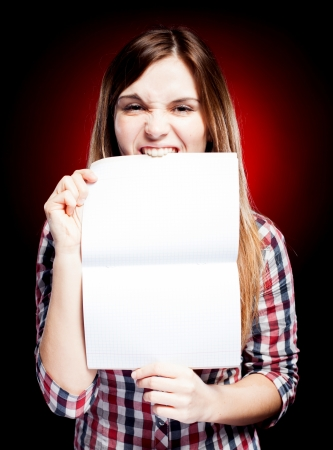 Disappointed and angry young girl holding open exercise book and bites photo