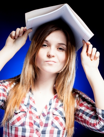 Disappointed and upset young girl holding exercise book on her head, symbol of school problems photo