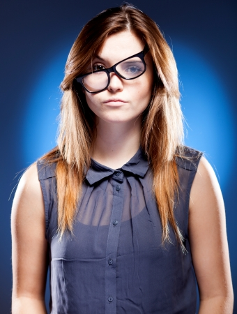 unsatisfied: Disappointed young woman with large nerd glasses has objections Stock Photo