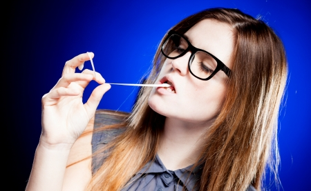 objections: Portrait of strict young woman with large nerd glasses and chewing gum Stock Photo
