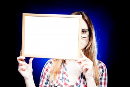 Smiling woman with large nerd glasses holding empty frame, copyspace photo