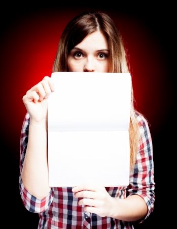 Surprised young girl holding open exercise book Stock Photo
