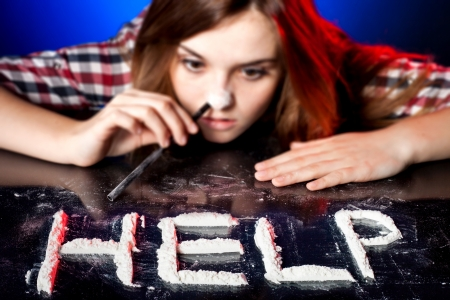 druggie: Woman snorting cocaine or amphetamines, symbol of help Stock Photo