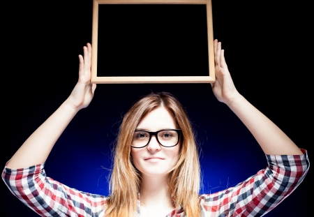 Woman with large nerd glasses holding wooden frame over her head photo