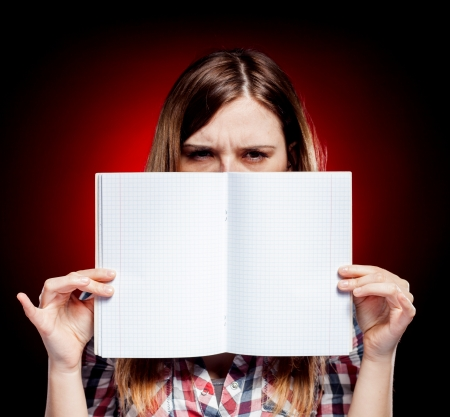 Disappointed and angry young girl holding open exercise book photo
