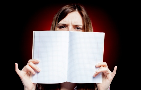 Disappointed and sad young girl holding open exercise book photo