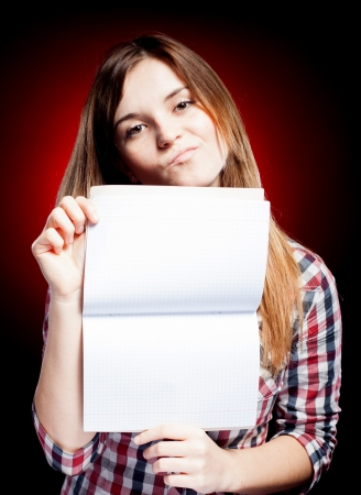 Disappointed young girl holding open exercise book photo