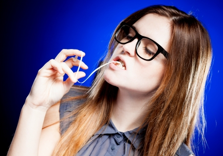 Portrait of strict young woman with large nerd glasses and chewing gum photo