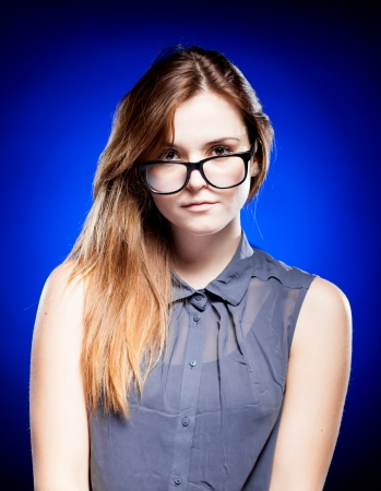 Pretty young woman looking through the nerd glasses photo