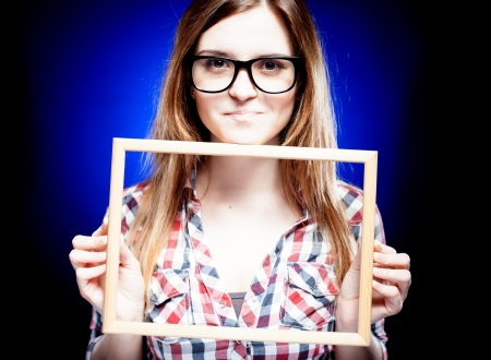 Smiling woman with large nerd glasses holding wooden frame photo