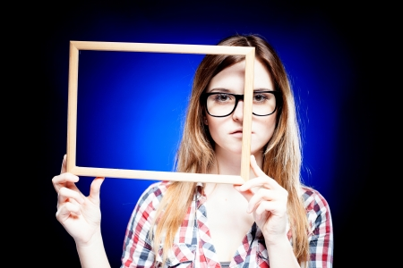 cropping: Serious woman with large nerd glasses holding wooden frame