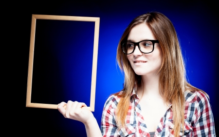 Smiling woman with large nerd glasses looking left and holding wooden frame