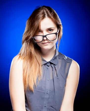 Strict young woman looking through the nerd glasses