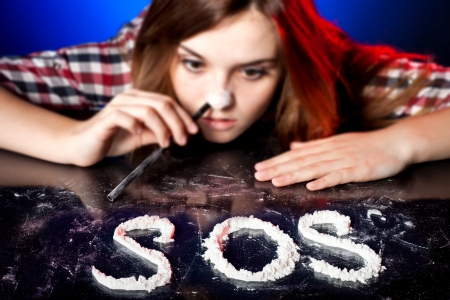 druggie: Woman snorting cocaine or amphetamines, symbol of drug problem with sos sign Stock Photo