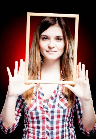 Young woman wearing plaid shirt holding wooden frame around her face photo