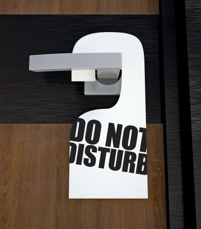 Door hanger Do not disturb message hanged on handle photo