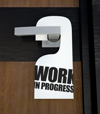 Door hanger Work in progress message hanged on handle photo