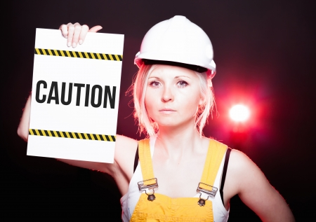 overhaul: Caution sign placed on information board and worker woman