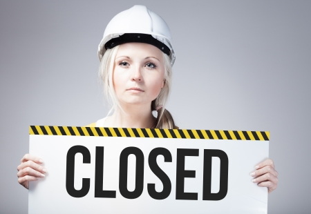 Closed sign held by a worker photo