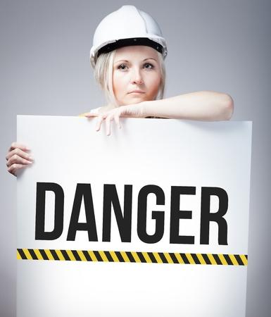 mujer trabajadora: Muestra del peligro en el cartel de la informaci�n y de la mujer trabajadora Foto de archivo