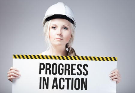 overhaul: Progress in action sign held by a worker Stock Photo