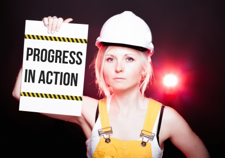 overhaul: Progress in action sign placed on information board and worker woman Stock Photo