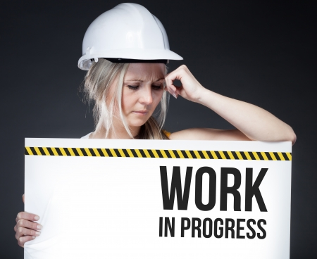 Work in progress sign on information board with thinking worker photo