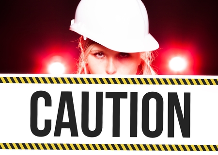 Worker holding caution sign placed on information board photo