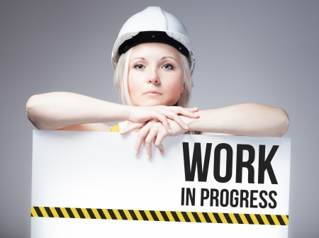 overhaul: Worker holding work in progress sign placed on information board
