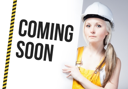 Worker holding coming soon sign placed on information board photo