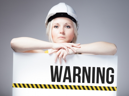 overhaul: Worker holding warning sign placed on information board