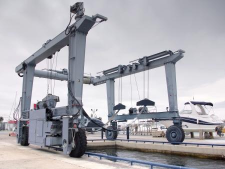 Crane to lifting boats at harbor or marina photo