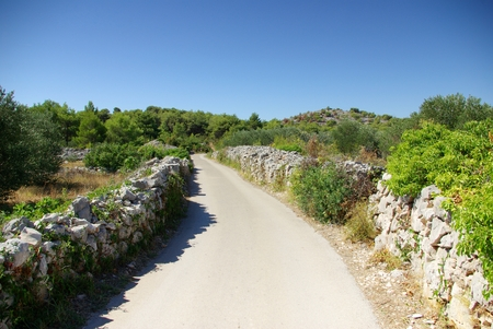 Narrow winding asphalt road between the rocks, Croatia Dalmatia Tribunj photo