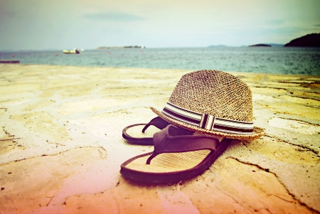 sandles: Beach sandals and straw hat by the sea, Croatia Dalmatia Tribunj Stock Photo