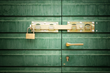Golden lock, padlock and handle on green door, detail photo