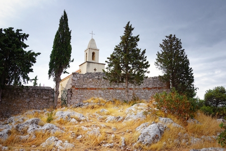Old small church and stone walls on hill photo