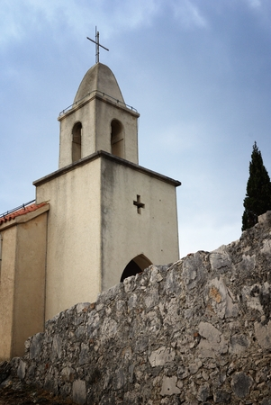 Old small church, tower belfry and stone wall photo