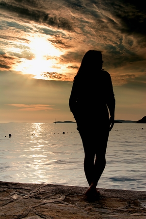sillhouette: Silhouette woman figure and sunset on the beach