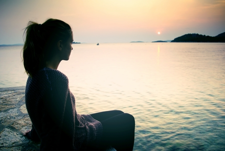 longing: Young woman sitting on the beach at sunset, a symbol of dreams and longing Stock Photo