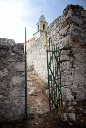 Open gate in old stone wall with church  photo